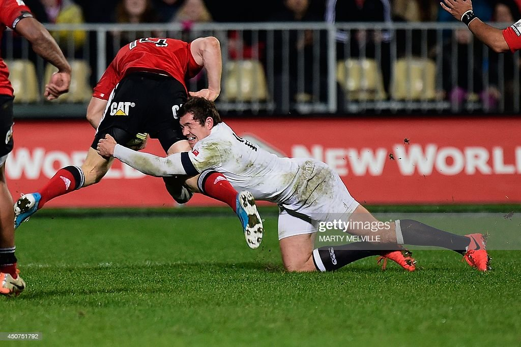 England's fullback Alex Goode (R) tackles Canterbury Crusaders right wing Johnny McNicholl during their rugby union match at AMI Stadium in Christchurch on June 17, 2014.