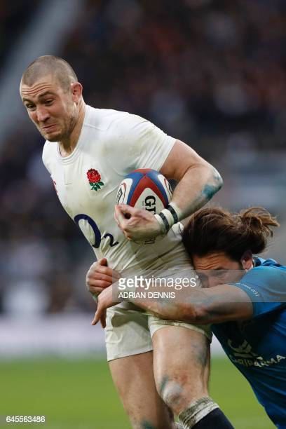 England's fullback Mike Brown is tackled by Italy's centre Michele Campagnaro during the Six Nations international rugby union match between England...