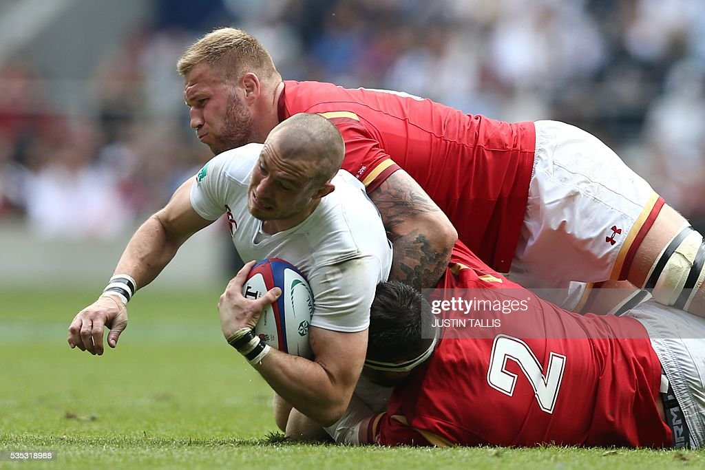 England's full-back Mike Brown (L) is tackled by Wales' flanker Ross Moriarty (top) and Wales' hooker Scott Baldwin (R) during the international rugby union match between England and Wales at Twickenham Stadium in west London on May 29, 2016. / AFP / JUSTIN