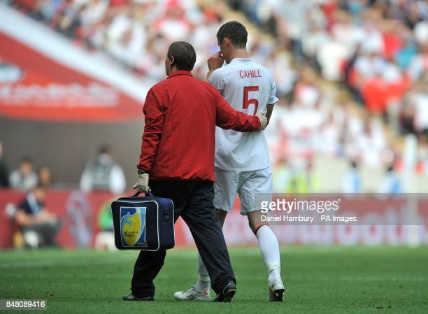 England's Gary Cahill leaves the field injured after a push by Belgium's Dries Mertens