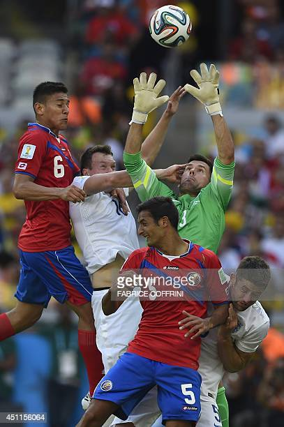 England's goalkeeper Ben Foster makes a save from Costa Rica's midfielder Celso Borges as England's defender Gary Cahill and England's defender Phil...