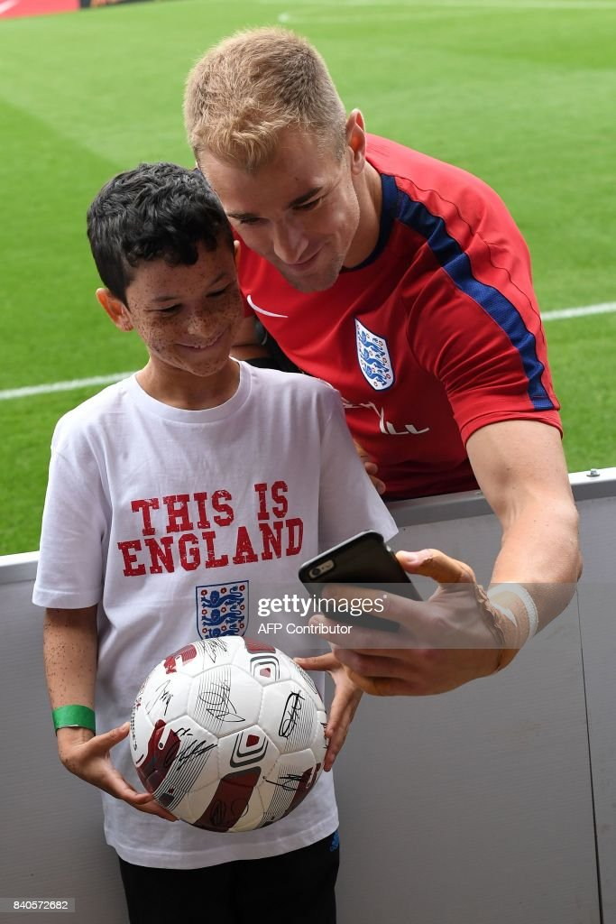 England's goalkeeper Joe Hart poses for a photograph with a young fan following a training session at St George's Park in Burton-on-Trent on August 29, 2017, as part of an England football team media day ahead of their 2018 FIFA World Cup qualifier matches against Malta on September 1 and Slovakia on September 4. / AFP PHOTO / Paul ELLIS / NOT