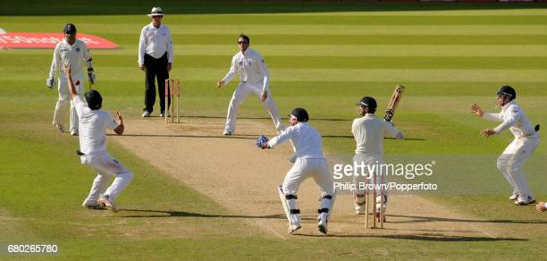 England's Graeme Swann watches as India's Rahul Dravid is caught by Alastair Cook for 13 during the 4th Test match at the Oval cricket ground in...