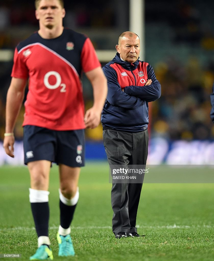 England's head coach Eddie Jones (back R) watches the team's warm-up session prior to their third and final rugby union Test match against host Australia in Sydney on June 25, 2016. / AFP / SAEED