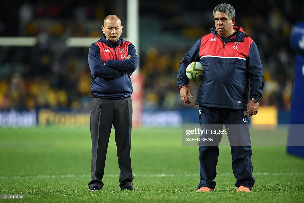 England's head coach Eddie Jones (L) watches the team's warm-up session prior to their third and final rugby union Test match against host Australia in Sydney on June 25, 2016. / AFP / SAEED