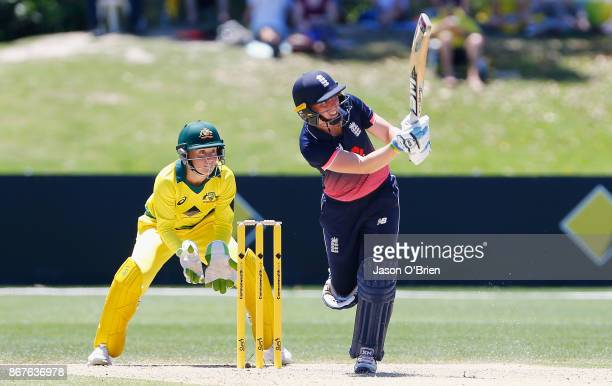 England's Heather Knight plays a reverse sweep as Australia's Alyssa Healy looks on during the Women's International One Day match between Australia...