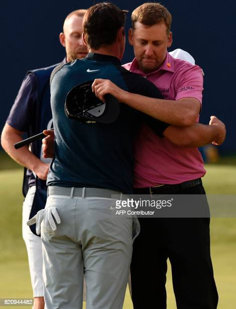 England's Ian Poulter and US golfer Brooks Koepka embrace on the 18th green after their third rounds on day three of the Open Golf Championship at...