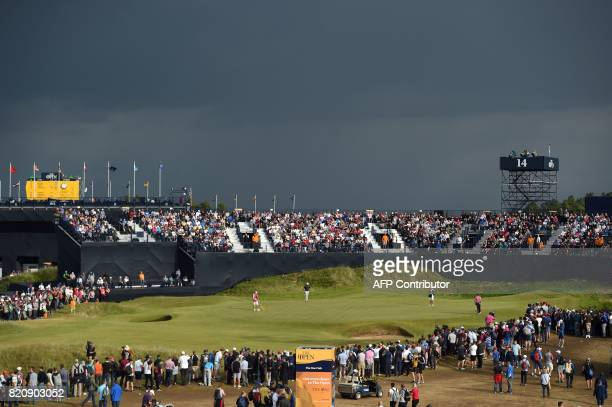 England's Ian Poulter and US golfer Brooks Koepka play on the 14th green under stormy skies during their third rounds on day three of the Open Golf...