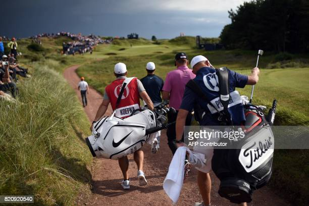 England's Ian Poulter and US golfer Brooks Koepka walk to the 12th green during their third rounds on day three of the Open Golf Championship at...