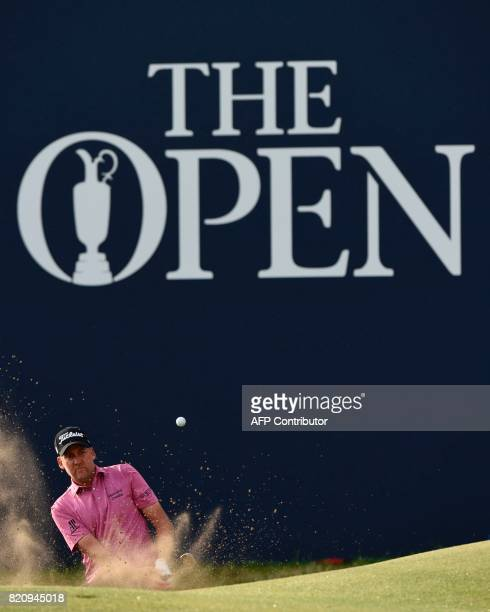 England's Ian Poulter plays from a greenside bunker to the 18th green during his third round on day three of the Open Golf Championship at Royal...