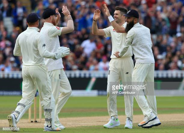 England's James Anderson celebrates with teammates after taking the wicket of West Indies' Kieran Powell during play on day 3 of the first Test...
