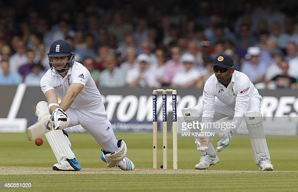 Englands James Anderson hits a reverse sweep shot as Sri Lanka wicketkeeper Prasanna Jayawardene looks on during the second days play in the first...