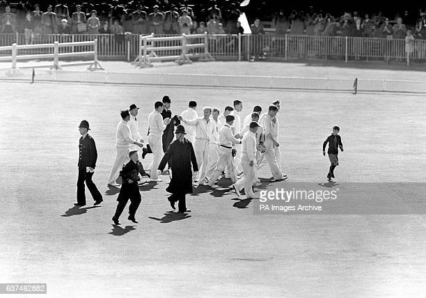England's Jim Laker leads his teammates off the pitch after taking all ten of Australia's second innings wickets to win the match