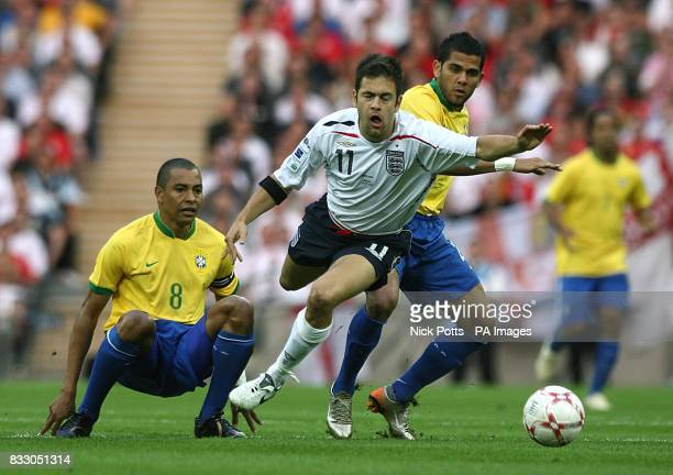 England's Joe Cole is fouled by Brazil's Daniel Alves and Gilberto Silva