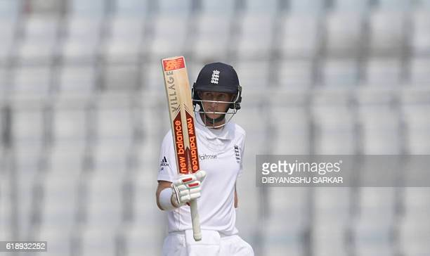 England's Joe Root celebrates after scoring a halfcentury during the second day of the second Test cricket match between Bangladesh and England at...