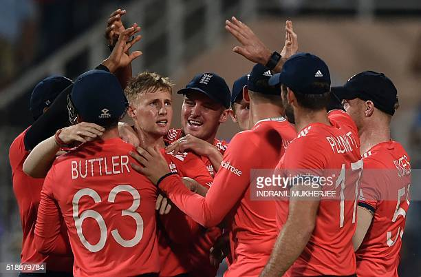 England's Joe Root is congratulated by teammates after the wicket of West Indies's Chris Gayle during the World T20 cricket tournament final match...