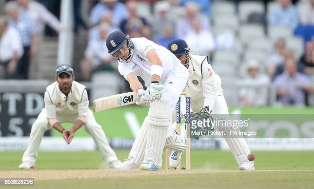 England's Joe Root plays a shot watched by India's Mahendra Dhoni and Virat Kohli during the Fourth Investec Test at Emirates Old Trafford Manchester