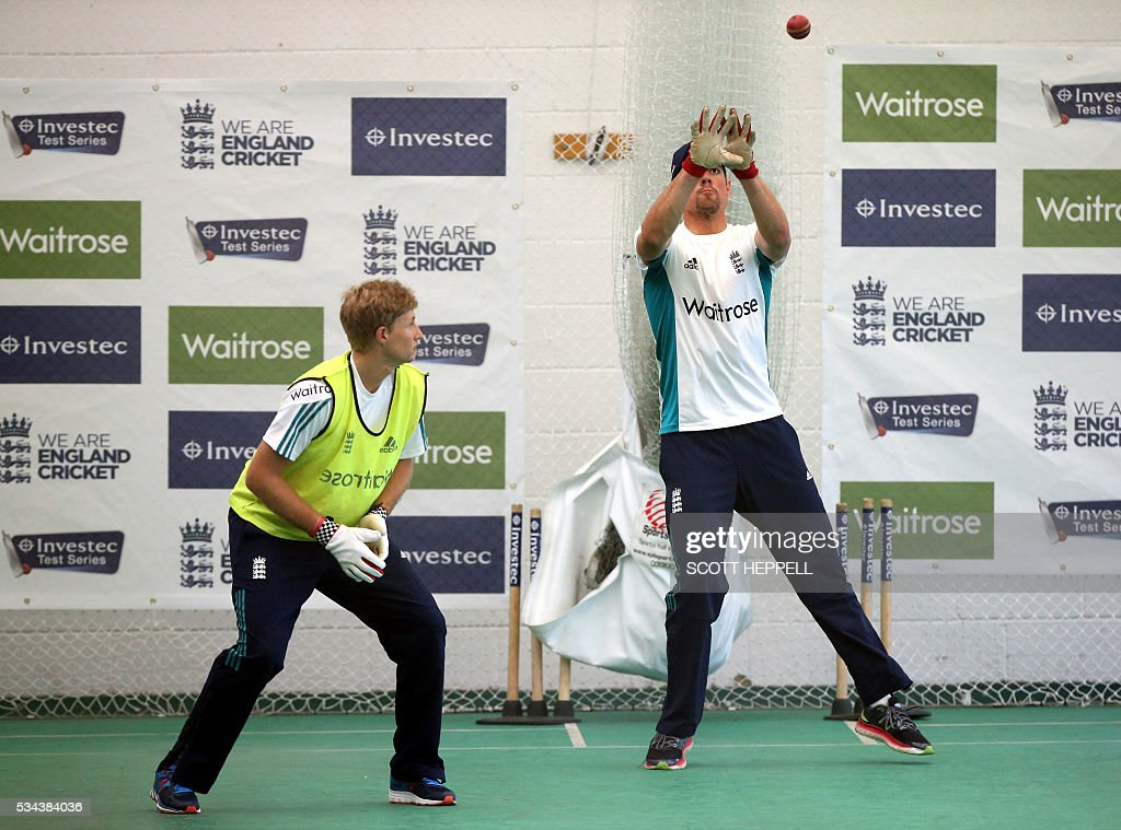 England's Joe Root (L) watches as England's captain Alastair Cook catches a ball during an indoor practice session ahead of the second cricket Test match between England and Sri Lanka in Chester-le-Street, north east England on May 26, 2016. England may come into the second Test against Sri Lanka in Durham on the back of a crushing win in the series opener, but according to Stuart Broad the hosts have still to hit top form. England are set to play Sri Lanka in a second test cricket match on May 27. / AFP / SCOTT