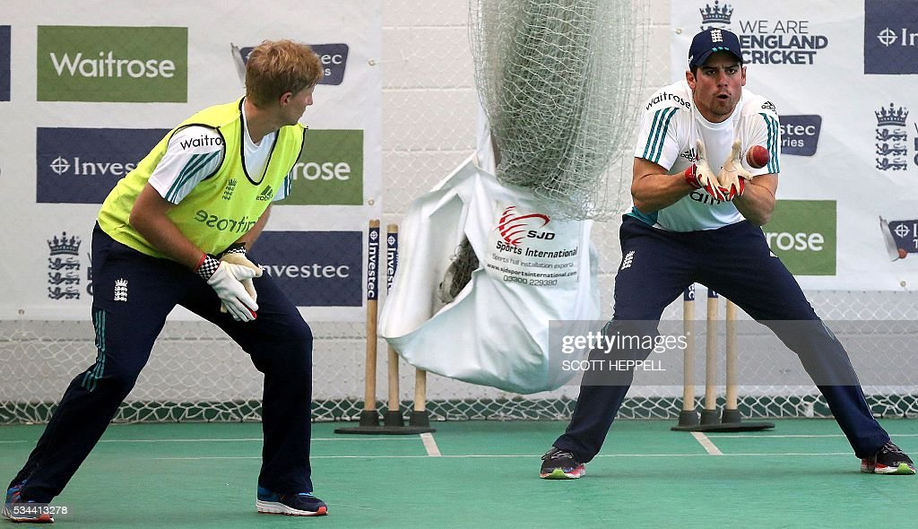 England's Joe Root (L) watches as England's captain Alastair Cook catches a ball during an indoor practise session ahead of the second cricket Test match between England and Sri Lanka in Chester-le-Street, north east England on May 26, 2016. England may come into the second Test against Sri Lanka in Durham on the back of a crushing win in the series opener, but according to Stuart Broad the hosts have still to hit top form. England are set to play Sri Lanka in a second test cricket match on May 27. / AFP / SCOTT