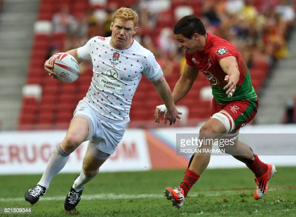 CORRECTION England's John Brake runs past a Portugal player during their match at the Singapore Rugby Sevens tournament on April 16 2016 / AFP /...