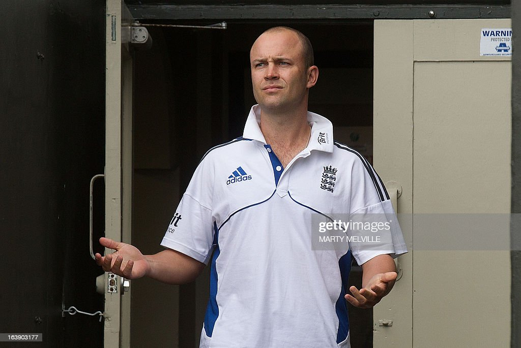 England's Jonathan Trott checks the weather as rain halts play during day five of the international cricket Test match between New Zealand and England played at the Basin Reserve in Wellington on March 18, 2013. AFP PHOTO / Marty MELVILLE