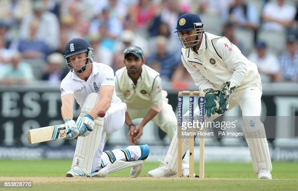 England's Jos Buttler hits for 4 watched by India's Mahendra Dhoni and Virat Kohli during the Fourth Investec Test at Emirates Old Trafford Manchester