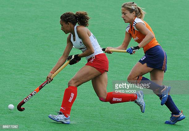 England's Kerry Williams with Wieke Dijkstra of the Netherlands makes a clearing run during the Women's Champions Trophy hockey match in Sydney on...
