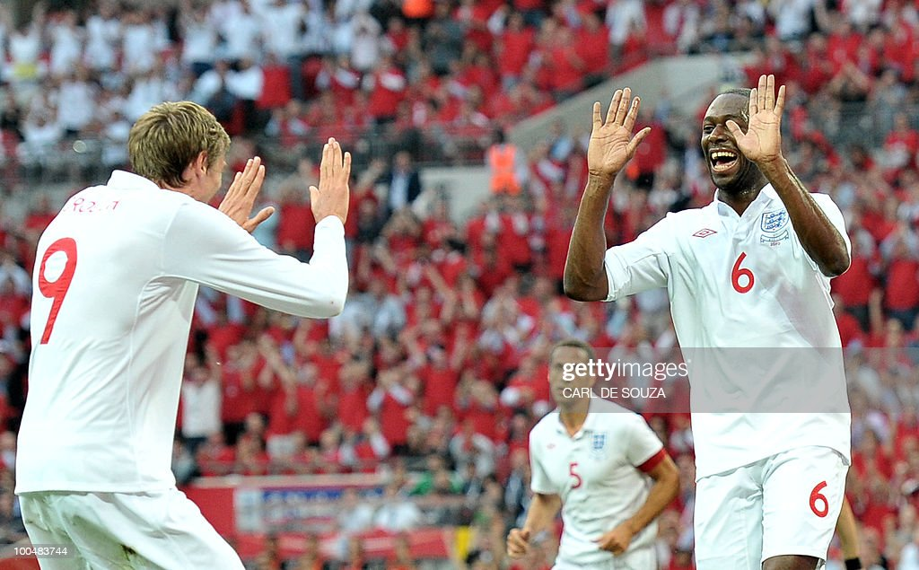 England's Ledley King (R) celebrates with England's Peter Crouch after scoring his goal during their international friendly football match at Wembley Stadium in London on May 24, 2010 AFP PHOTO/Carl de Souza