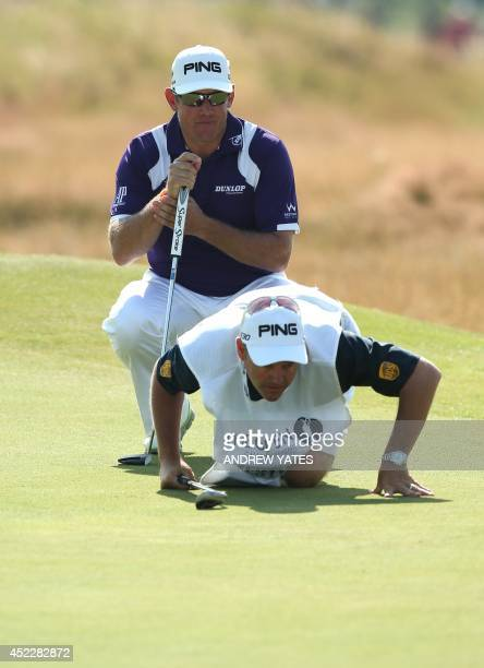 England's Lee Westwood and caddie Billy Foster line up a putt on the 7th green during his first round on the opening day of the 2014 British Open...