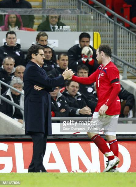 England's Manager Fabio Capello shakes hands with Wayne Rooney as he is substituted