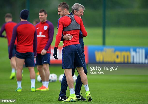 England's manager Roy Hodgson reacts as he embraces England's striker Jamie Vardy during a team training session in Watford north of London on June 1...