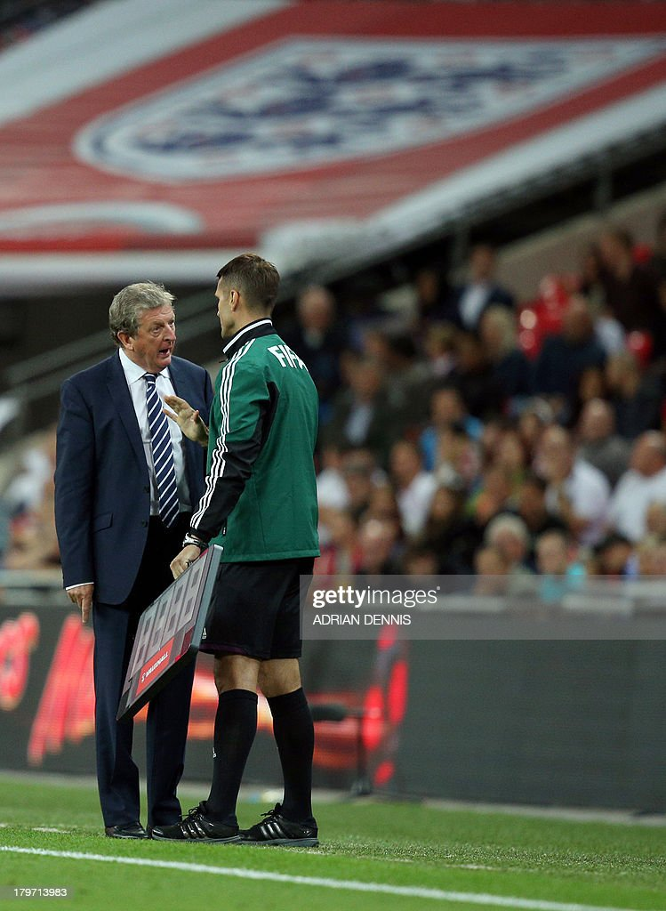England's Manager Roy Hodgson (L) speaks with the fourth official after Referee Ivan Kruzliak (not pictured) booked England's Daniel Welbeck against Moldova during the World Cup 2014 Group H qualifying football match between England and Moldova at Wembley Stadium in north London on September 6, 2013. England won the game 4-0. Welbeck will be suspended for England's next game. AFP PHOTO / ADRIAN DENNIS USE