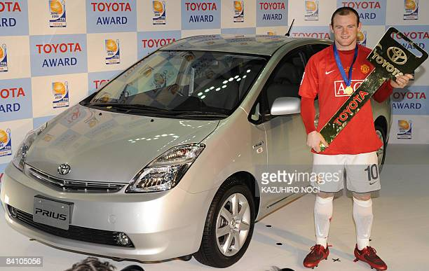 England's Manchester United forward Wayne Rooney stands next to a Toyota Prius presented as Most Valuable Player after the final match against...