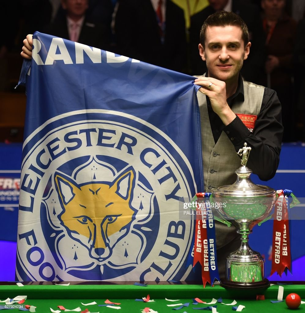 England's Mark Selby holds a Leicester City football club flag next to the trophy after beating China's Ding Junhui in the final of the World Snooker Championship at the Crucible theatre in Sheffield, northern England, on May 2, 2016. / AFP / PAUL