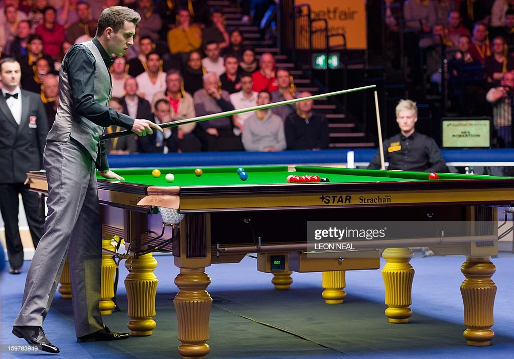 England's Mark Selby (L) lines up a shot as Australia's Neil Robertson (R) watches from his seat during the Masters Snooker final at Alexandra Palace in north London on January 20, 2013.