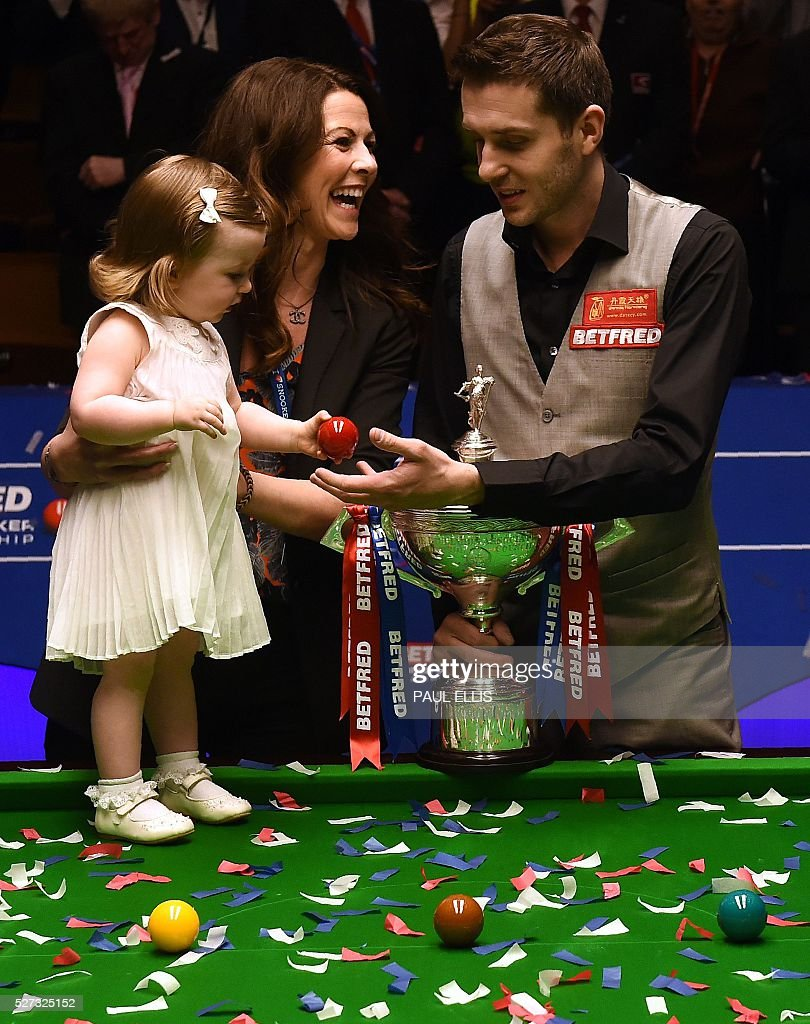 England's Mark Selby (R) poses with wife Nikki and daughter Sophia (L) and the trophy after beating China's Ding Junhui in the final of the World Snooker Championship at the Crucible theatre in Sheffield, northern England, on May 2, 2016. / AFP / PAUL