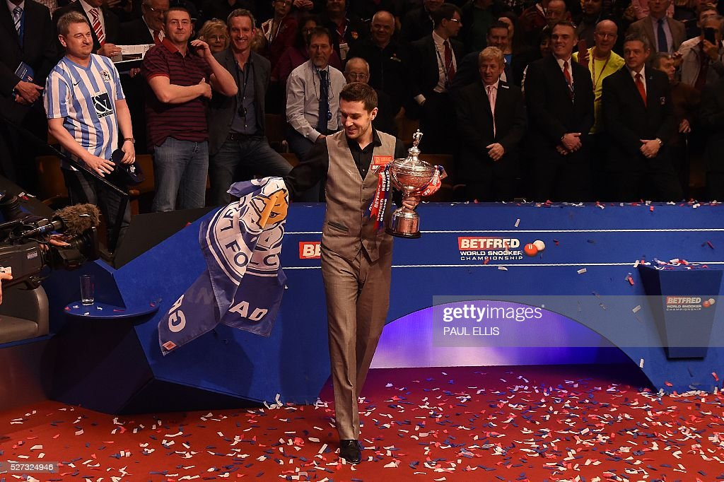 England's Mark Selby takes a Leicester City Football Club flag as he holds the trophy after beating China's Ding Junhui in the final of the World Snooker Championship at the Crucible theatre in Sheffield, northern England, on May 2, 2016. / AFP / PAUL