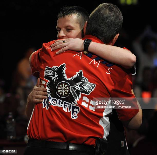 England's Martin Adams is congratulated by Dave Chisnall during the World Darts Championship at Frimley Green Surrey