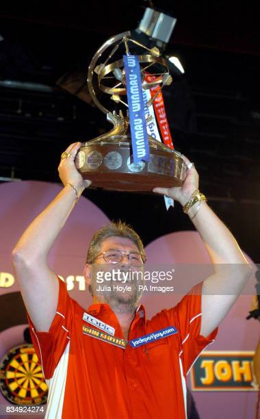 England's Martin Adams lifts the trophy aloft as he celebrates his victory at the Winmau World Masters at The Spa Bridlington