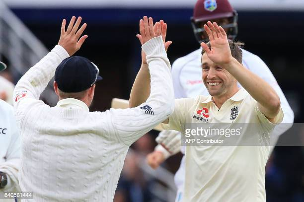 England's Mason Crane celebrates with England's Chris Woakes the wicket of West Indies' Roston Chase for 30 on the fifth and final day of the second...