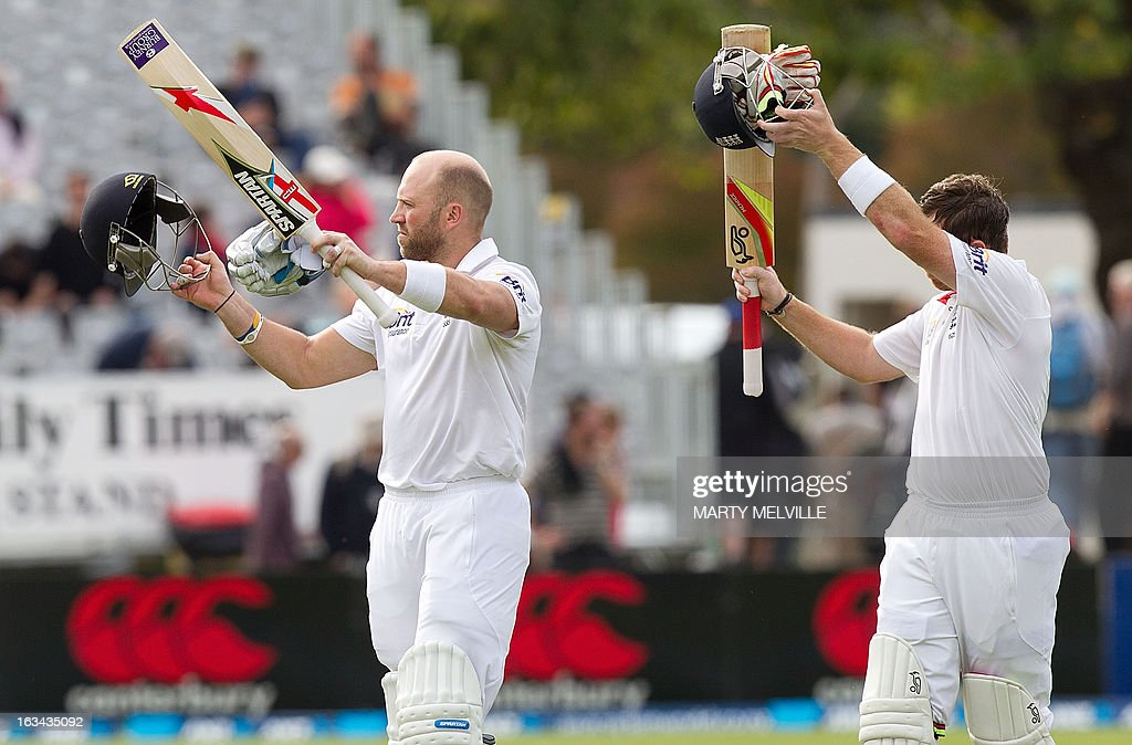 England's Matt Prior (L) and Ian Bell wave to the fans as they walk from the field at the end of the game during day four of the first international cricket Test match between New Zealand and England played at the University Oval park in Dunedin on March 10, 2013. AFP PHOTO / Marty MELVILLE