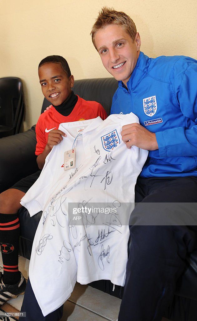 England's Michael Dawson poses with Aubrey, aged 12, during a visit to an orphanage in Tlhabane Township near, Rustenburg on June 15, 2010.