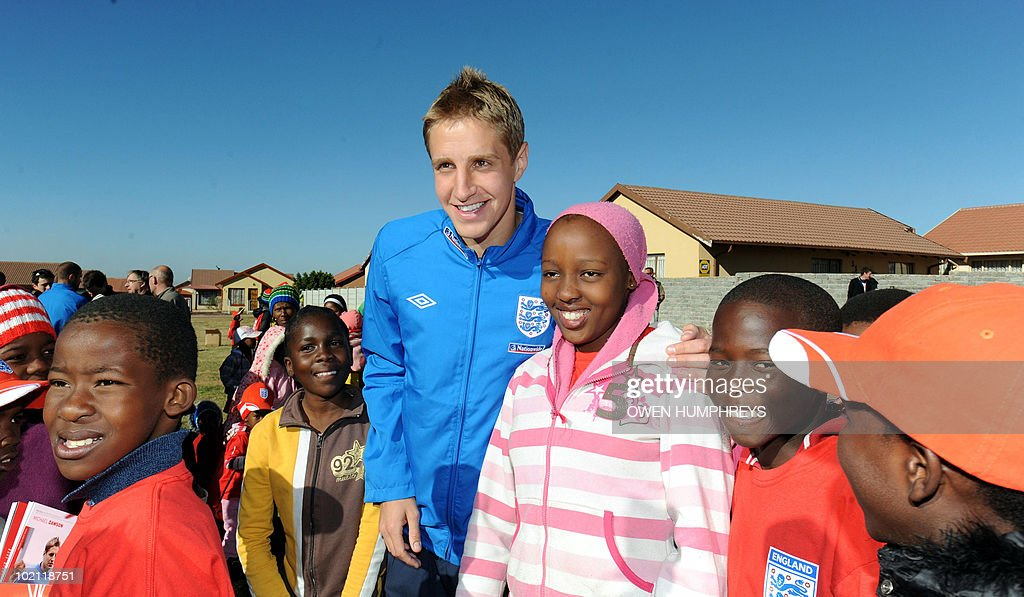 England's Michael Dawson poses with children during a visit to the Tlhabane Township near Rustenburg, South Africa on June 15, 2010.