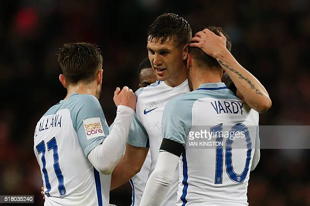 England's midfielder Adam Lallana England's defender John Stones and England's striker Jamie Vardy celebrate after Vardy scored the opening goal...