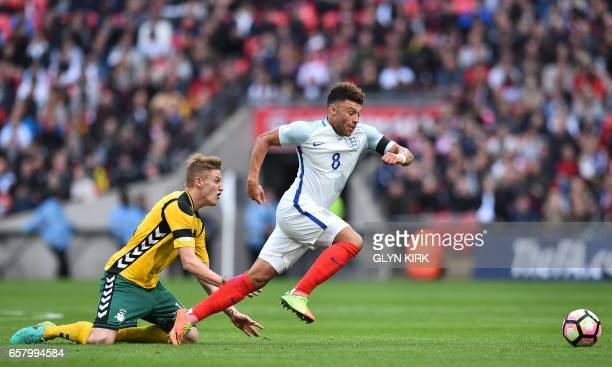 England's midfielder Alex OxladeChamberlain runs away from Lithuania's midfielder Vykintas Slivka during the World Cup 2018 qualification football...