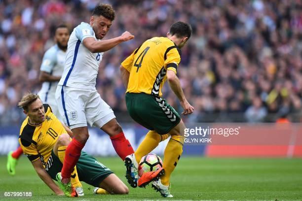 England's midfielder Alex OxladeChamberlain vies with Lithuania's midfielder Arturas Zulpa and Lithuania's defender Tadas Kijanskas during the World...