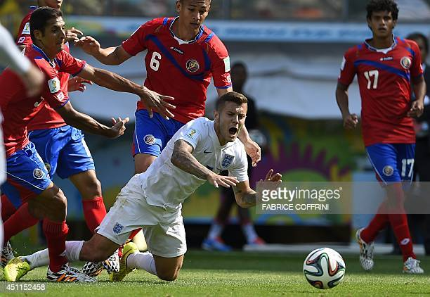 England's midfielder Jack Wilshere falls onto the pitch as Costa Rica's defender Oscar Duarte looks on during the Group D football match between...