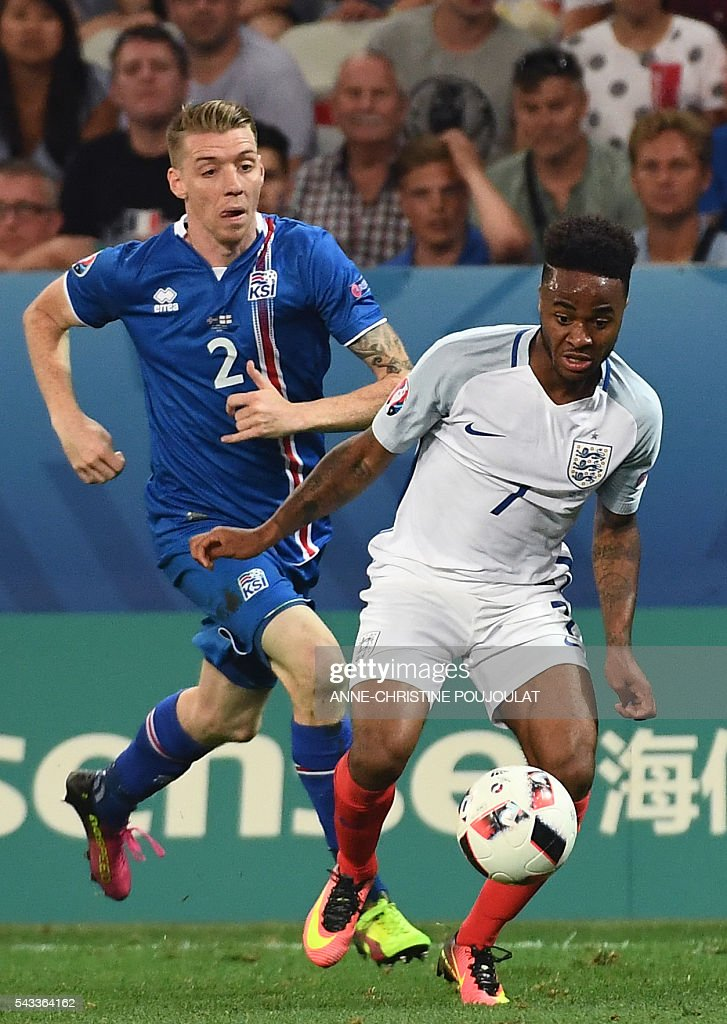 England's midfielder Raheem Sterling (R) and Iceland's defender Birkir Saevarsson vie for the ball during Euro 2016 round of 16 football match between England and Iceland at the Allianz Riviera stadium in Nice on June 27, 2016. / AFP / ANNE