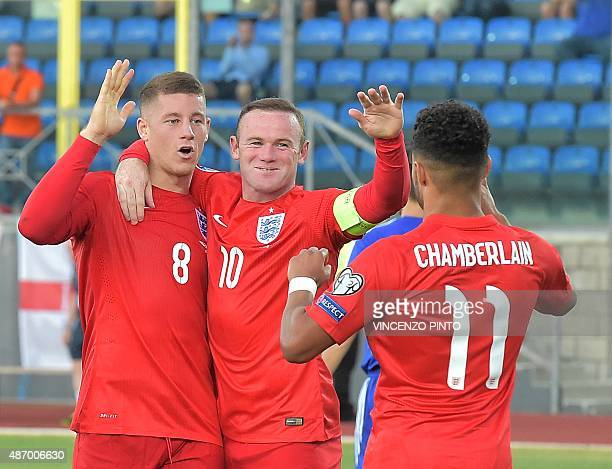 England's midfielder Ross Barkley celebrates with England's forward Wayne Rooney and England's forward Alex Oxlade Chamberlain after scoring during...