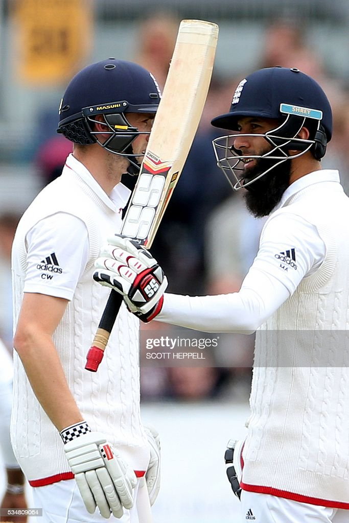 England's Moeen Ali (R) celebrates scoring 50 runs with Chris Woakes (L) on the second day of the second test cricket match between England and Sri Lanka at the Riverside in Chester Le Street, north east England on May 28, 2016. / AFP / SCOTT